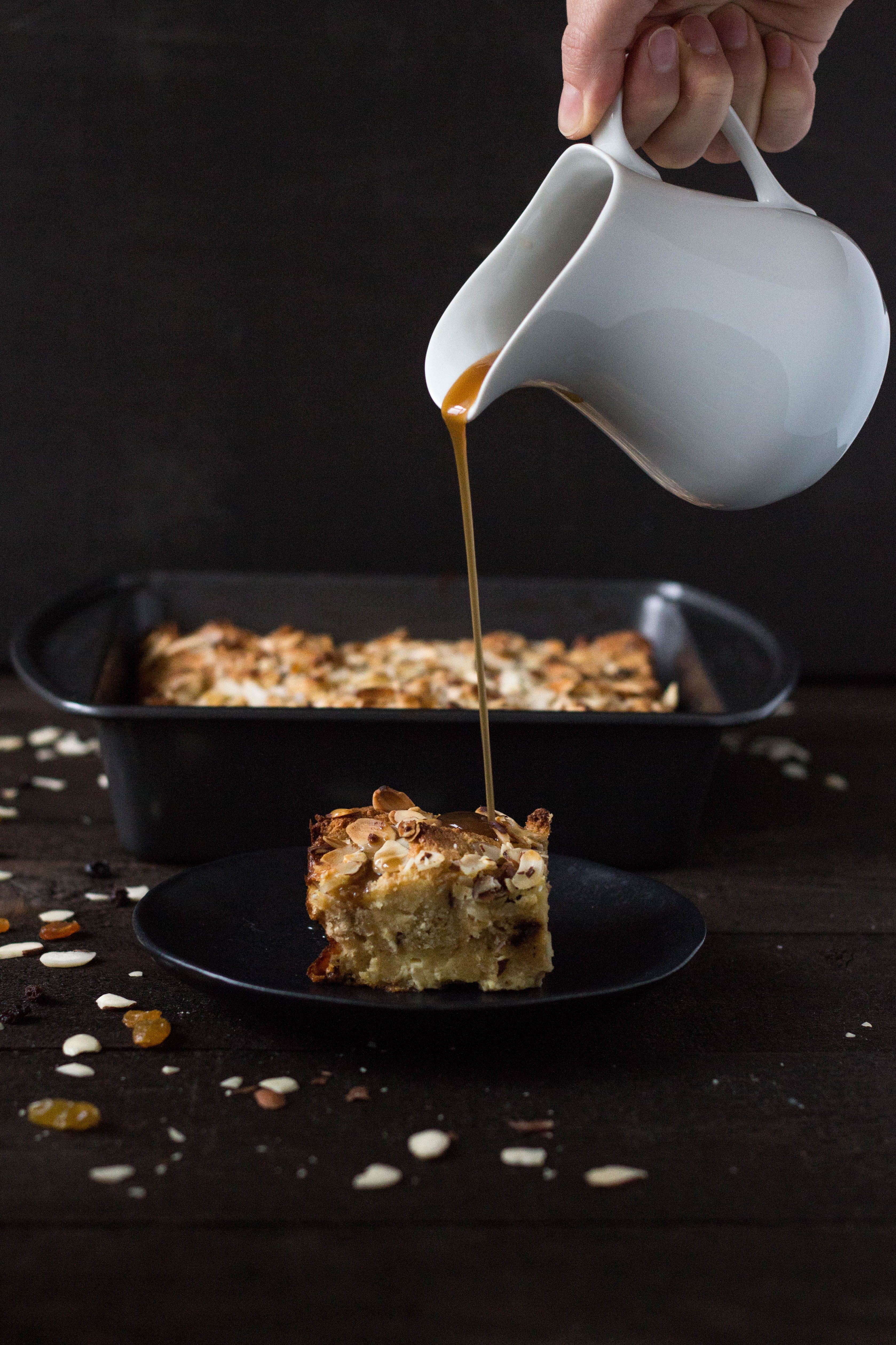 Straight on shot of pouring Brandy Sauce on a slice of Panettone Bread Pudding with the rest of the pudding in the background on a dark wood surface.